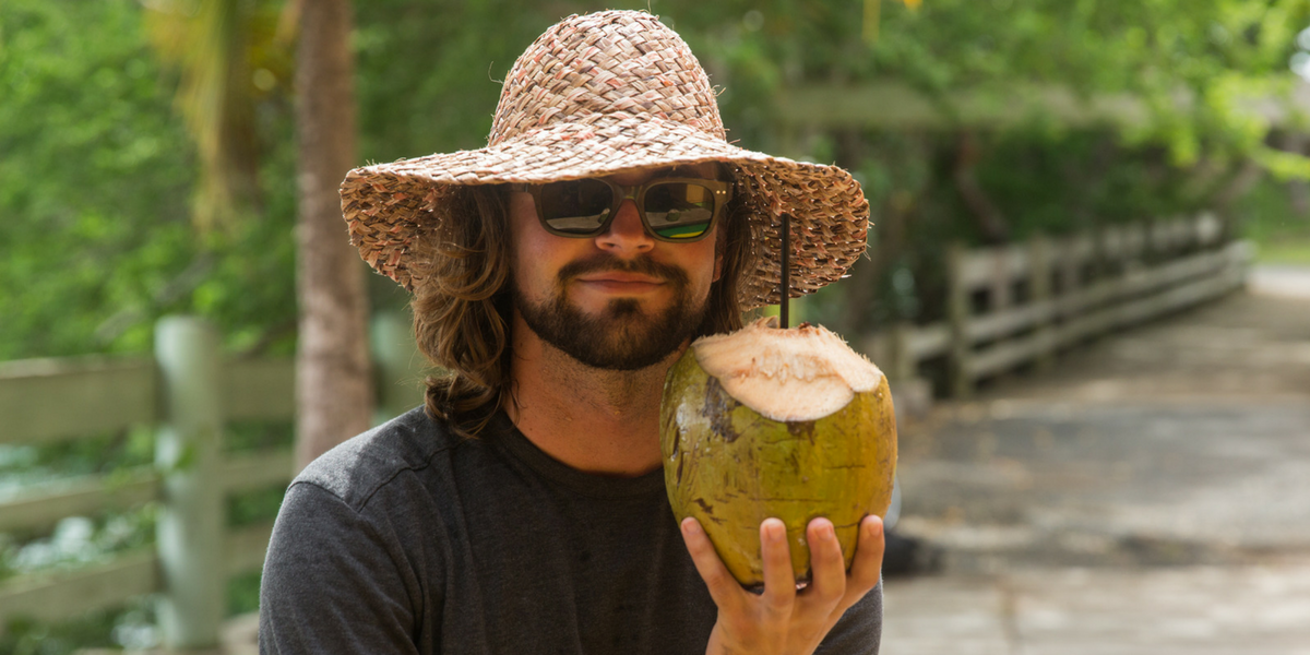 Adam Fricke posing with a coconut.
