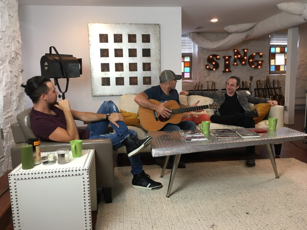 Three guys talking holding guitar