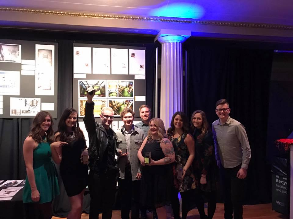 The Parachute Media team posing for a picture, holding their addy awards.