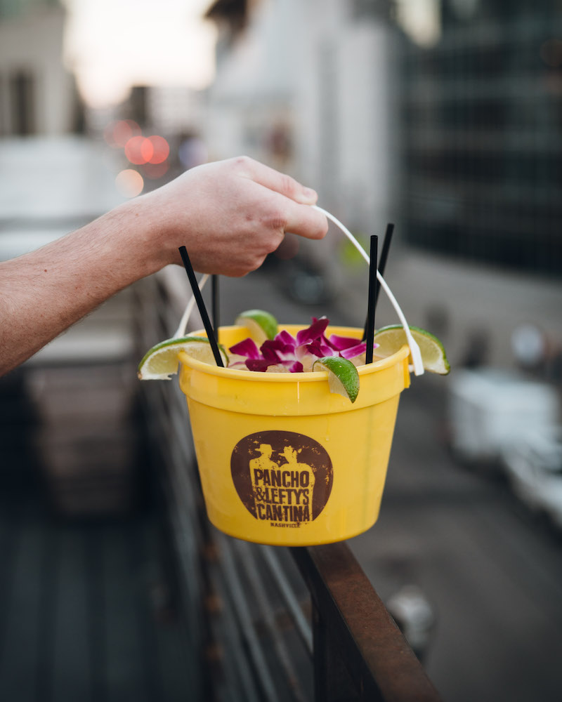 A yellow bucket filled with a margarita.