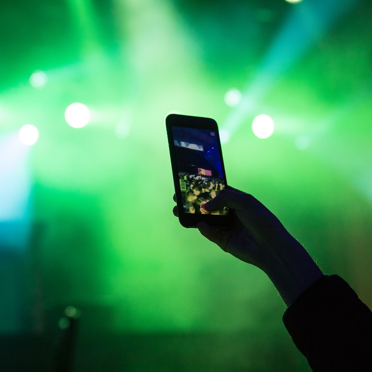 A silhouette of a hand filming a concert using an iPhone