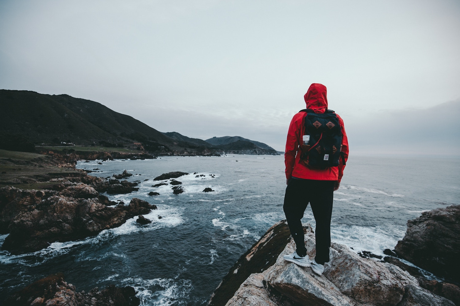person in red jacket standing on cliff looking out into the distance