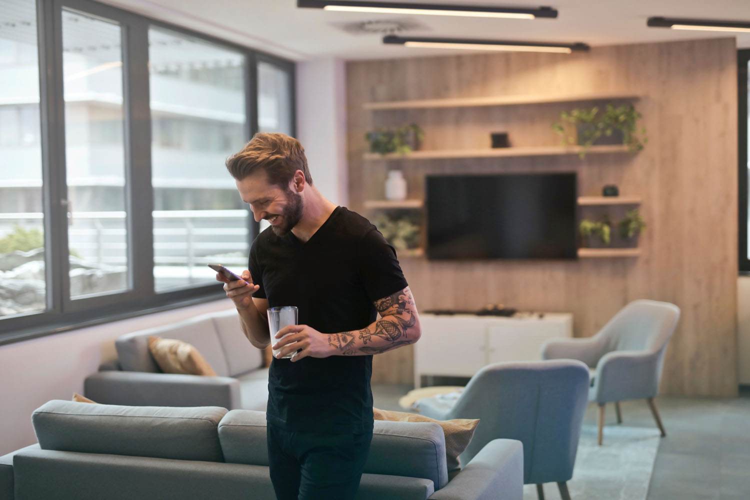 Image of man drinking coffee and laughing while looking at his phone community management..