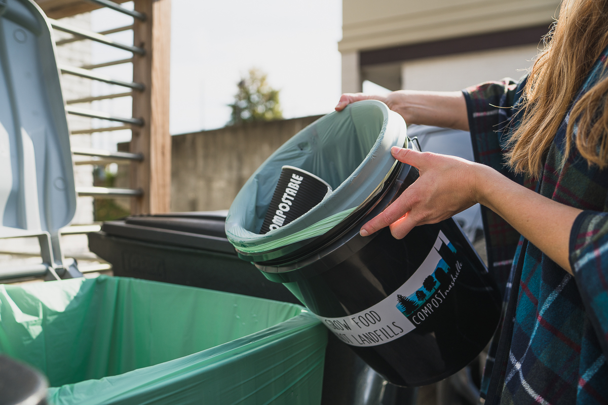 an office compost bin being dumped into a larger compost receptacle