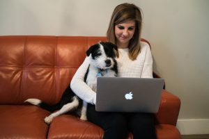 A dog leaning on a woman working on a laptop