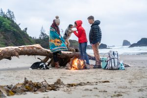 3 people and a god on the beach with a campfire