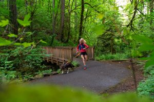 girl running on trail with dog