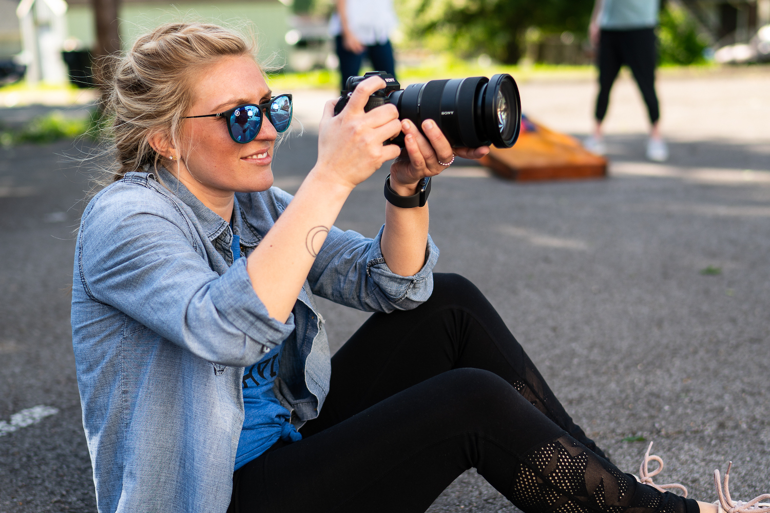 girl sitting down and taking a picture with a camera