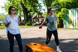 two girls playing corn hole outside