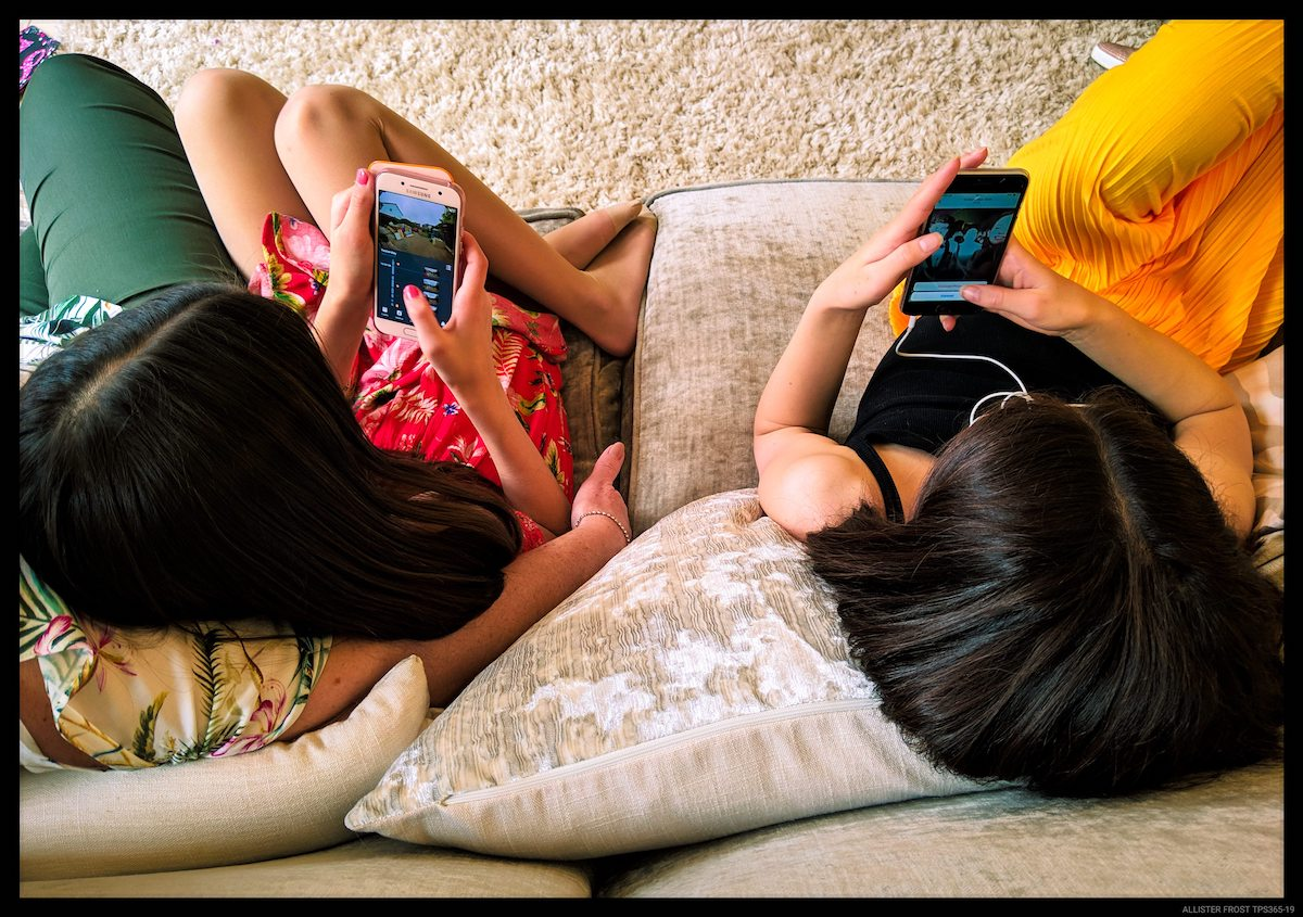 Two girls on their phone on the couch