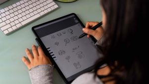An image taken from over the shoulder of an employee while they work on an iPad drawing.
