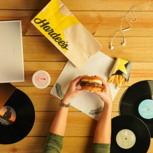 An overhead image from a Hardee's photoshoot. This image features a Hardee's paper bag and a woman's arms holding a burger.