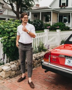 Man posed besides antique red car in front of a house.