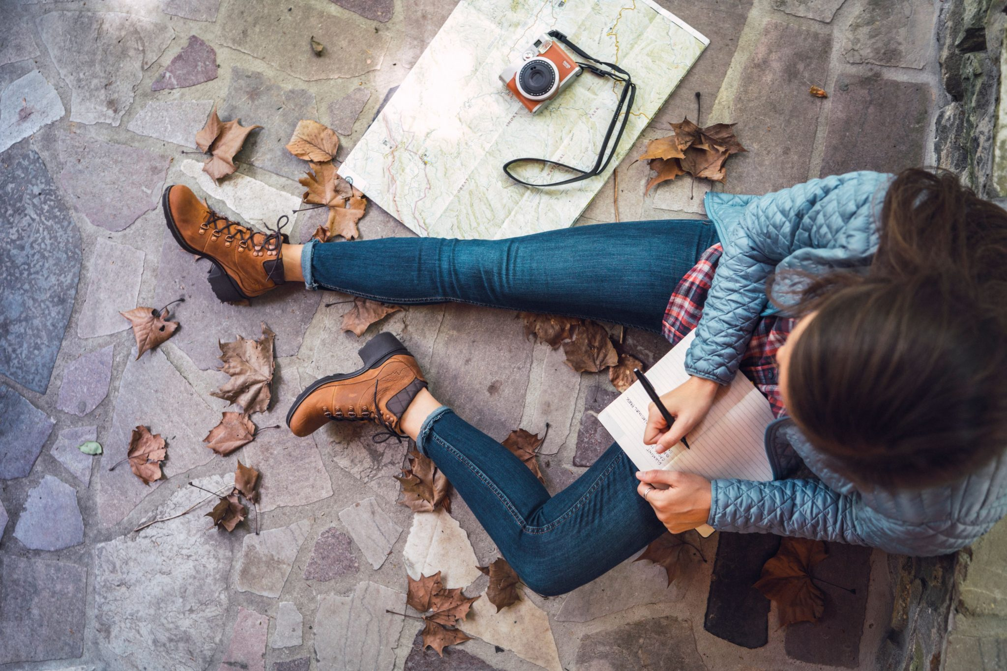 An overhead image of a woman writing in a journal wearing Merrell shoes.