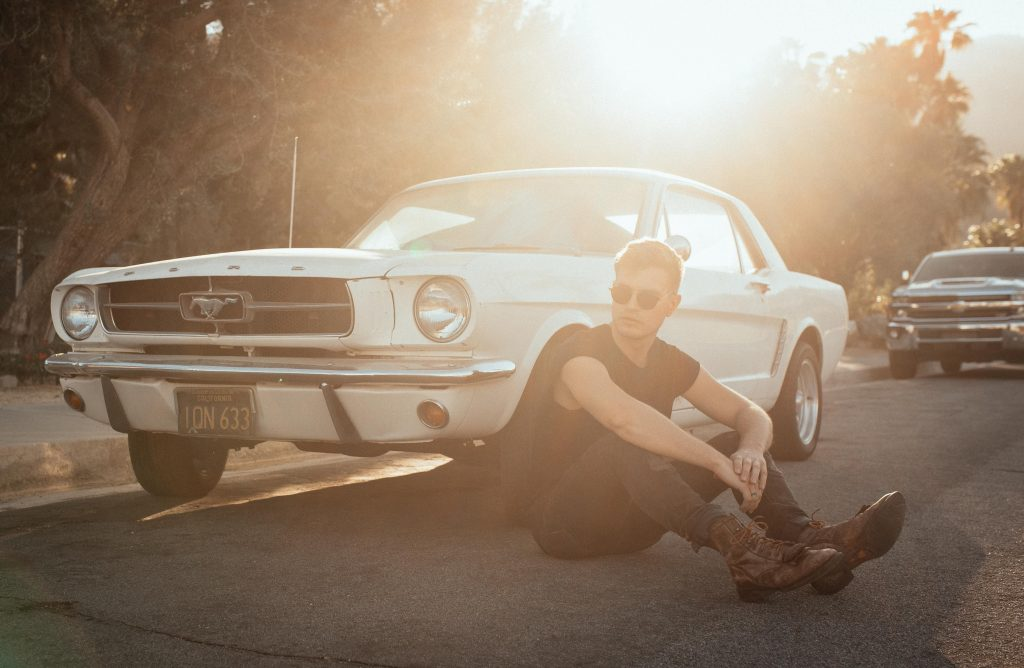 A stylized image of a man sitting on the ground beside an antique Mustang.