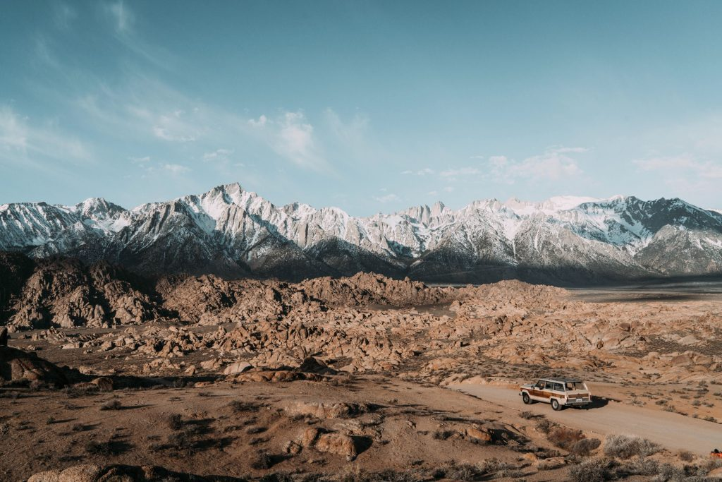 LAndscape photo of a desert and snow capped mountains in the background. In the bottom right of the image, a Jeep Wagoneer is positioned.