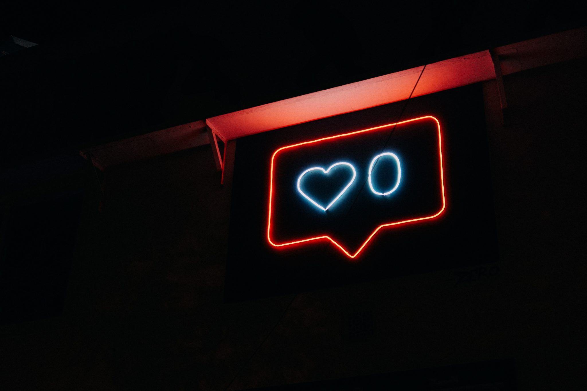 Photo of neon sign resembling the Instagram notification, it reads zero likes.