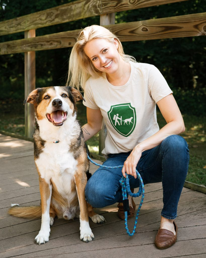An image of a girl wearing a Camping With Dogs t-shirt and smiling with her dog.
