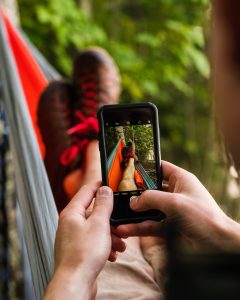 An image of a man in a hammock with a phone taking a picture