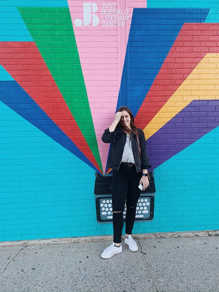 Becca in front of mural