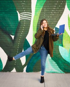 Becca in front of green/blue mural in Nashville, Tennessee, holding a laptop and cell phone.