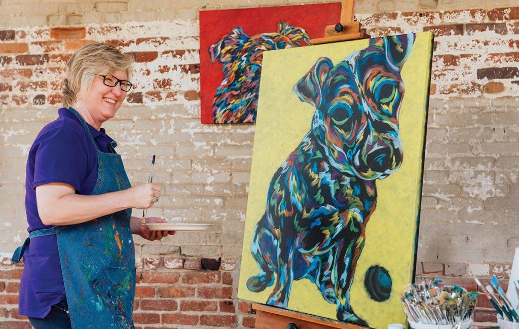 Image of artist with dog painting